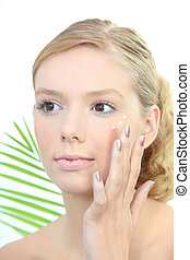 Young blond woman applying anti-wrinkles cream