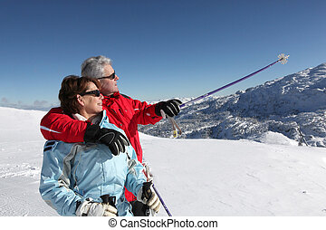 Older ski couple on a mountain