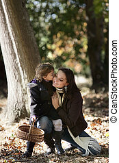 Little girl kissing her mum in woods