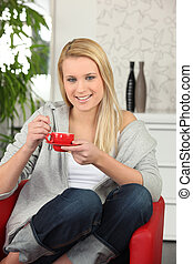Young woman having a cup of coffee at home