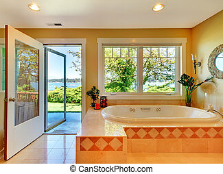 Yellow bathroom with lake view and large tub. - Large yellow...