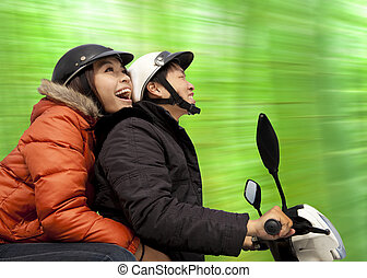 happy couple riding on the bike at spring time