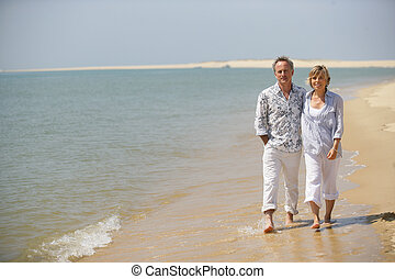 Middle-aged couple strolling along the shore