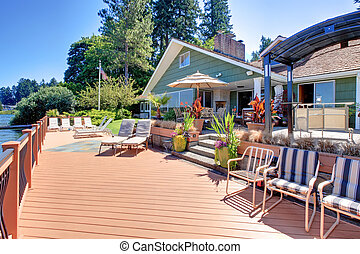 Lake fron house with large deck and outdoor living areas.
