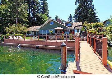 Lakefront green one story house with dock and large deck. -...
