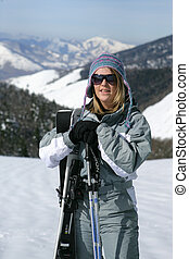 Female skier standing on a mountain
