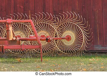 hay rake beside red barn - hay raking equipment next to a...