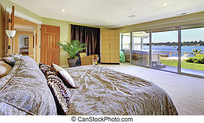 Large yellow bedroom with lake view and hot tub