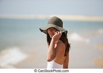 An attractive woman wearing a floppy hat at the beach