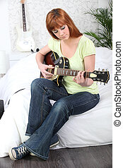 Young female guitarist at home