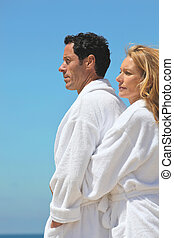 Profile view of couple by the sea wearing bathrobes