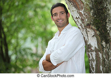 Man standing with his arms crossed under a large tree