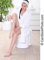 Woman removing leg hair in a bathroom