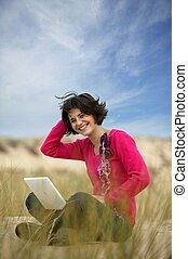 Brunette using laptop at the beach