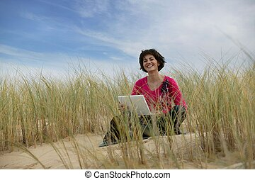 Woman using a laptop in a sand dune