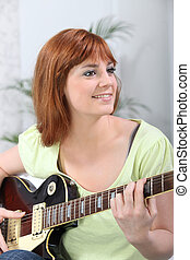 Young woman playing a guitar at home