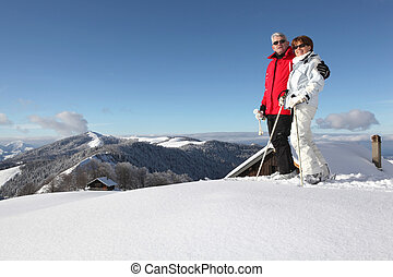 Middle-aged couple skiing
