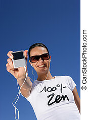 Woman listening to music outdoors with mp3 player