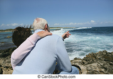 Senior couple pointing towards the sea