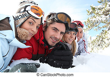 Ski couples lying in the snow