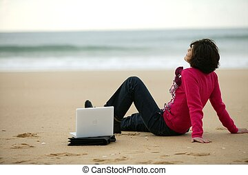 Woman on a beach with her laptop