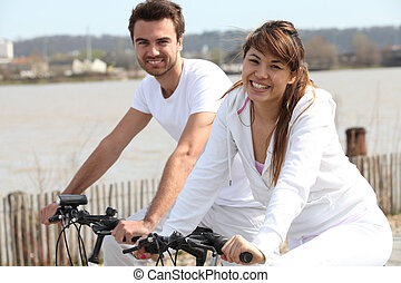 young couple doing bike near the sea