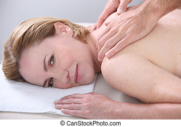 Woman being given a back massage and looking at us.