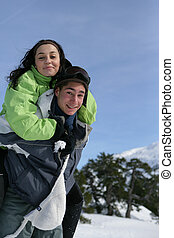 Smiling boy carrying his girlfriend on his back