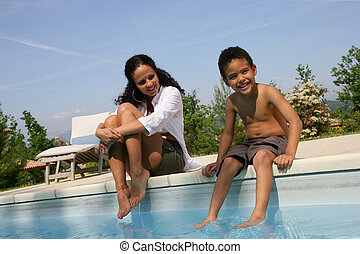 Mother and son dipping feet in swimming pool