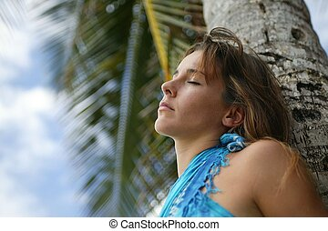 Woman leaning against palm tree