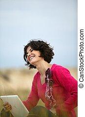 Happy brunette sat in a field with laptop