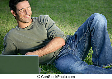 Happy man sat in field with laptop