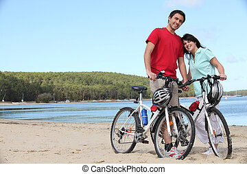 Young couple with bikes on a  beach