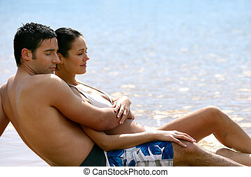 Embraced couple laid on the sand