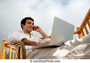 Man relaxing with laptop whilst sat in the garden
