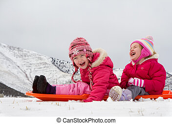 Two laughing kids sledding with a mountain scene in...