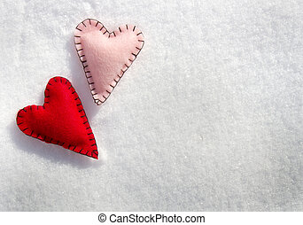 Two stitched hearts on snow - Two stitched hearts on a snowy...