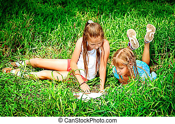 friends reading - Two cheerful girls reading books outdoors