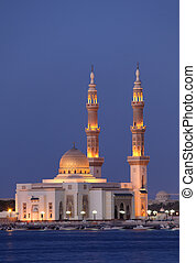 Mosque in Sharjah illuminated at dusk, United Arab Emirates