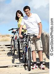 Couple taking their bikes to the beach