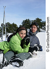 Young couple sat in snow