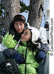 Teenage couple sitting on a ski slope