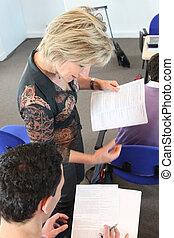 Teacher looking over her student's work