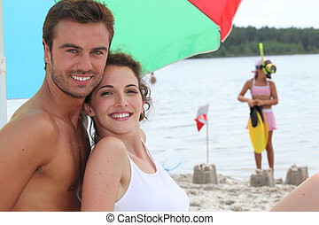 Couple on a sandy beach with daughter in the background