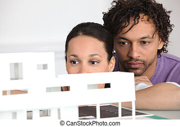 Couple looking at model housing