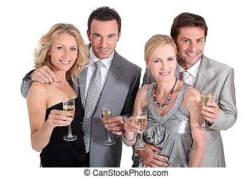 Double date: couples in party dress drinking champagne