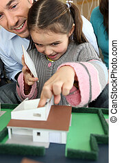 Family sat with model of new house