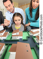 Young family looking at model housing