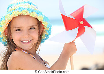 Little girl playing with wind toy on beach