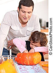 Dad and his daughter carving pumpkins in the kitchen